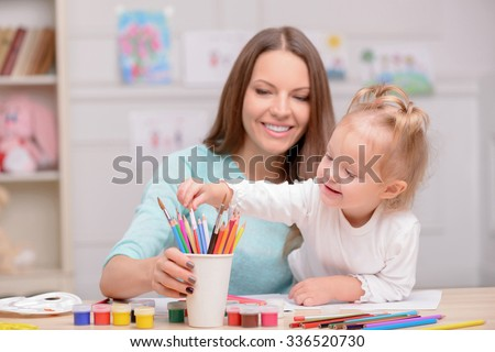Attractive young mother and her daughter are drawing. They are sitting at desk and laughing. The girl is taking a pencil from the cup