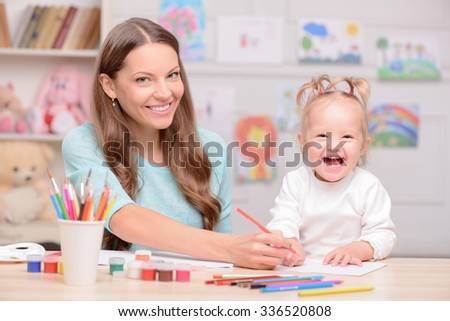 Attractive young mother and her small daughter are drawing pictures. They are sitting at the desk and smiling. The family is looking at the camera happily - stock photo