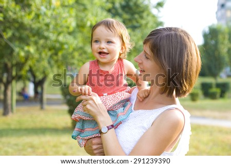 Attractive young mother holding a little girl in her arms - stock photo