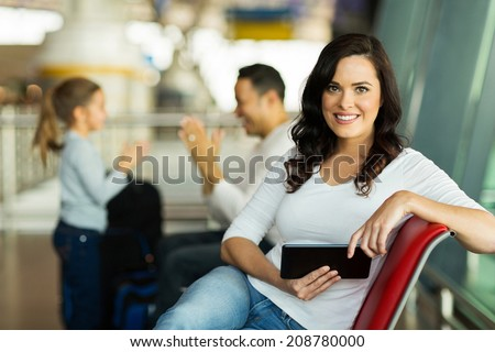 attractive young mother holding tablet computer at airport while waiting for their flight  - stock photo