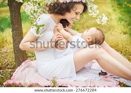 Attractive young mother playing with her baby - stock photo