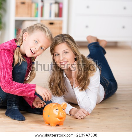 Attractive young mother teaching her little daughter to save as they lie on the floor together feeding coins into a piggy bank - stock photo