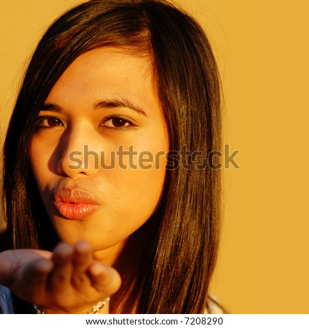 Attractive young multi racial woman blowing a kiss - stock photo