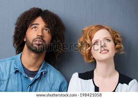 Attractive young multiracial couple standing thinking or watching something in the air with their heads tilted back and serious pensive expressions - stock photo