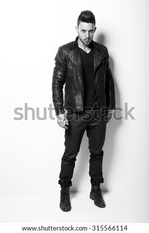 Attractive young muscle male model posing in black shirt and leather jacket. Fashion photo.