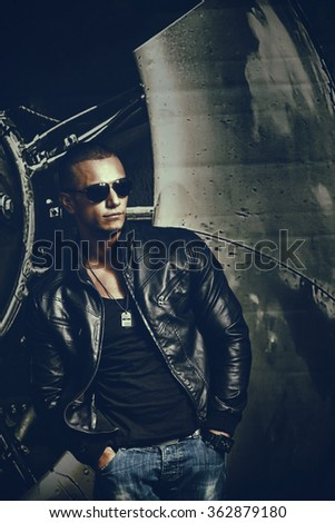 Attractive young muscle male model posing outdoors in black shirt and leather jacket. Fashion colors.  - stock photo