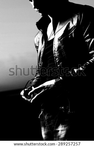 Attractive young muscle male model posing outdoors in black shirt and leather jacket.Fashion colors