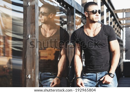 Attractive young muscle male model posing outdoors in black shirt and sunglasses .Fashion colors  - stock photo