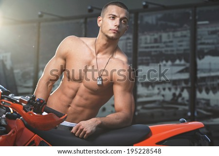Attractive young muscle male model posing outdoors in black shirt and sunglasses .Fashion colors
