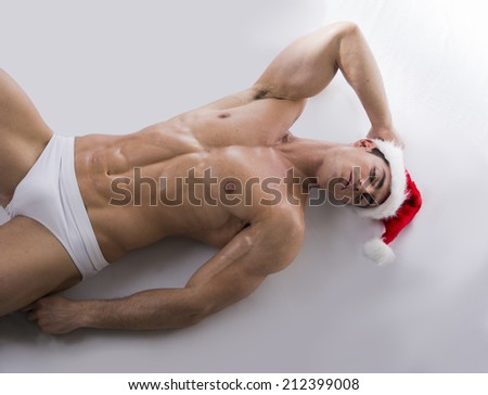 Attractive young muscle man laying on the floor with muscular ripped body in Santa Claus's red hat