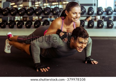 Attractive young muscular man doing push ups in gym, woman lying on him. Both smiling - stock photo