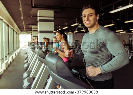 Attractive young muscular man in headphones running on a treadmill in gym, looking at camera and smiling - stock photo