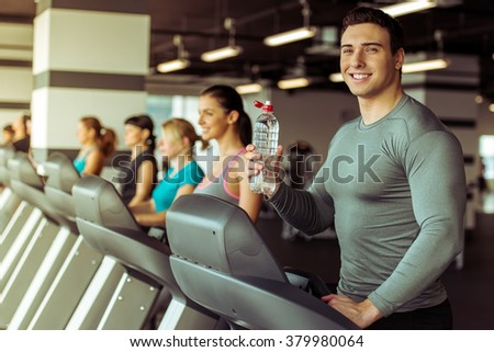 Attractive young muscular man running on a treadmill in gym, holding a bottle of water and smiling - stock photo