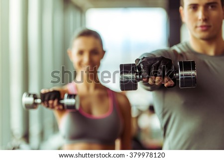 Attractive young muscular people working out with dumbbells in gym - stock photo