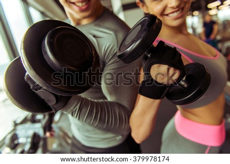 Attractive young muscular people working out with dumbbells in gym, looking at camera and smiling, close-up - stock photo