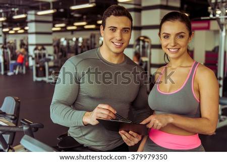 Attractive young muscular trainer consulting beautiful woman in gym. Both smiling - stock photo
