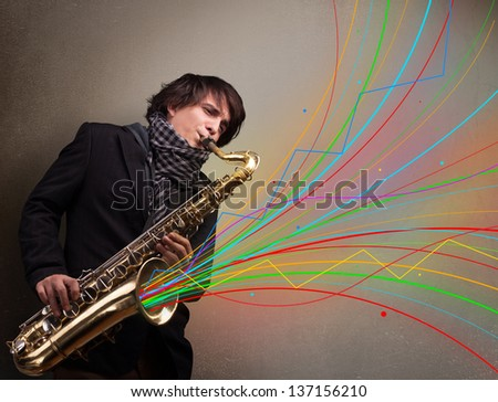 Attractive young musician playing on saxophone while colorful abstract lines exploding - stock photo