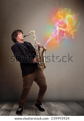 Attractive young musician playing on saxophone with colorful abstract fume comming out - stock photo