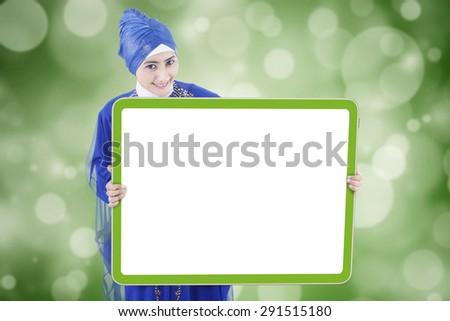 Attractive young muslim woman wearing islamic clothes and holding a blank banner, shot with defocused background - stock photo