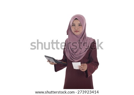Attractive young muslimah businesswoman calculating her expanditure. - stock photo