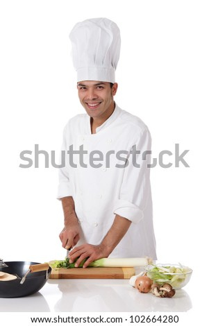 Attractive young nepalese chef male with uniform and hat, cutting a leek. Utensils and ingredients on table. Studio shot. White background. - stock photo