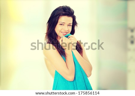 Attractive young nude woman covered by blue towel, getting ready for bath - stock photo