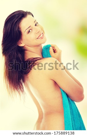 Attractive young nude woman covered by blue towel, getting ready for spa treatment - stock photo