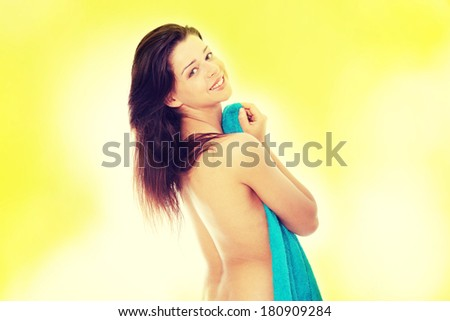 Attractive young nude woman covered by blue towel, getting ready for spa treatment, over green background  - stock photo