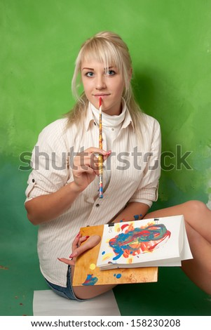 Attractive young painter on a green background - stock photo