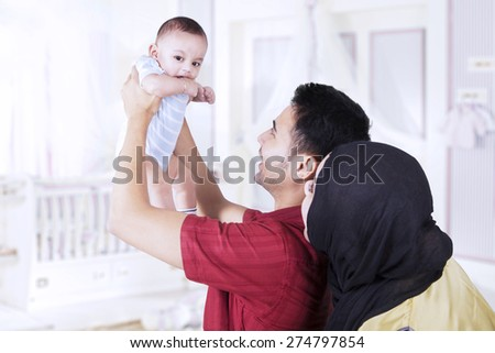 Attractive young parents holding their baby in the bedroom, shot at home - stock photo