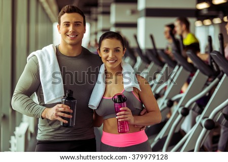 Attractive young people holding bottles of water, looking at camera and smiling while standing in gym - stock photo