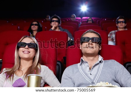 Attractive young people in 3D glasses watching a movie at the cinema - stock photo