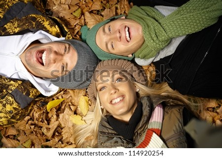 Attractive young people laying on ground among autumn leaves, smiling, having fun. - stock photo