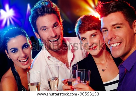 Attractive young people smiling happily in nightclub - stock photo