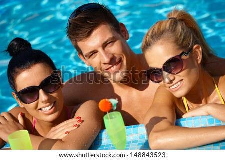 Attractive young people smiling in swimming pool, drinking cocktail.
