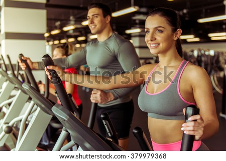Attractive young people working out on an elliptical trainer in gym and smiling - stock photo
