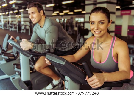 Attractive young people working out on an exercise bike in gym and smiling - stock photo