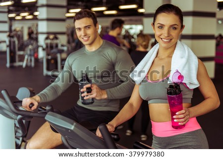 Attractive young people working out on an exercise bike in gym, holding bottle of water and smiling - stock photo