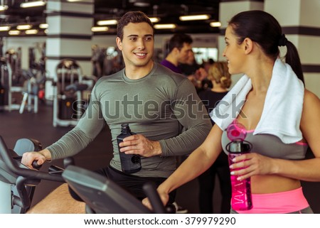 Attractive young people working out on an exercise bike in gym, holding bottle of water, talking and smiling - stock photo