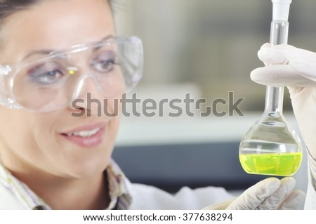 Attractive young PhD student scientist observing the green indicator color shift after the solution destillation in chemical laboratory