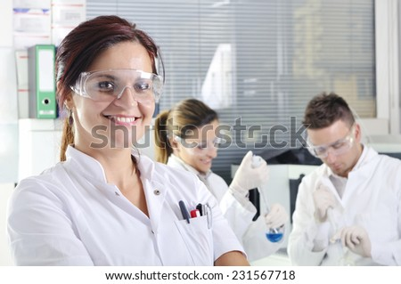 Attractive young PhD student scientist with two colleague out of focus behind her in chemical laboratory - stock photo