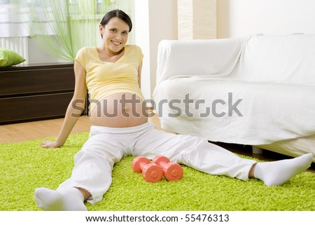 Attractive young pregnant woman exercising with dumbbells - stock photo