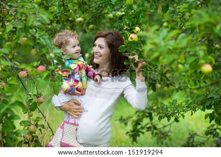 Attractive young pregnant woman holding her baby daughter under an apple tree in a fruit garden in autumn - stock photo