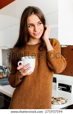 Attractive young  pretty  woman with white cup of tea looking out of the camera in the modern kitchen on sunny fall morning time.  - stock photo