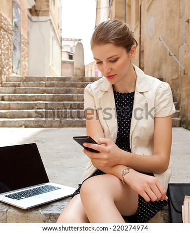 Attractive young professional business woman sitting on the steps of an old stone building using a smartphone and a laptop computer working outdoors. Connectivity and wireless internet browsing. - stock photo