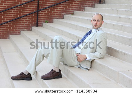 Attractive, Young Professional Serious and Mature Businessman Man Relaxing and Looking at the Camera (Full-Body)