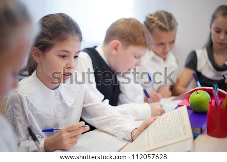 Attractive young pupils studying in the classroom with focus on adorable girl