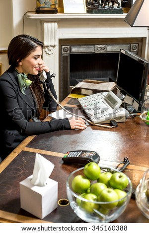 Attractive young receptionist on call - stock photo