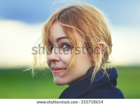 Attractive young red-haired woman in stylish clothes posing against nature background in summer smiling  - stock photo