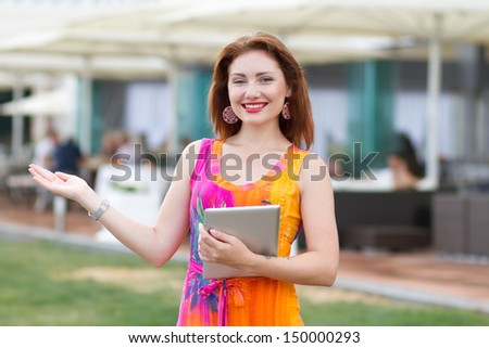 Attractive young red haired woman playing with her trendy tablet pc